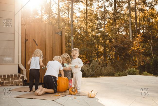 Children carving a pumpkin together