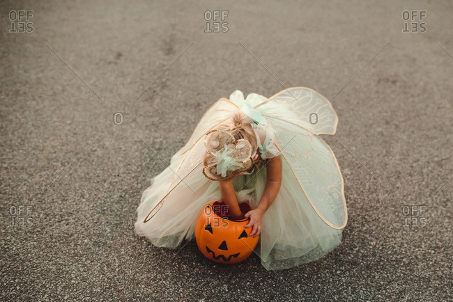 Little girl dressed as a fairy for Halloween looking through her bucket