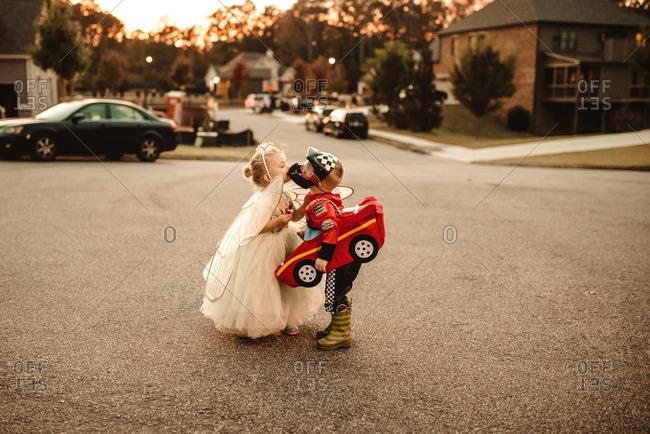 Children in Halloween costumes kissing
