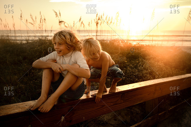 Little boys playing on a railing by the ocean