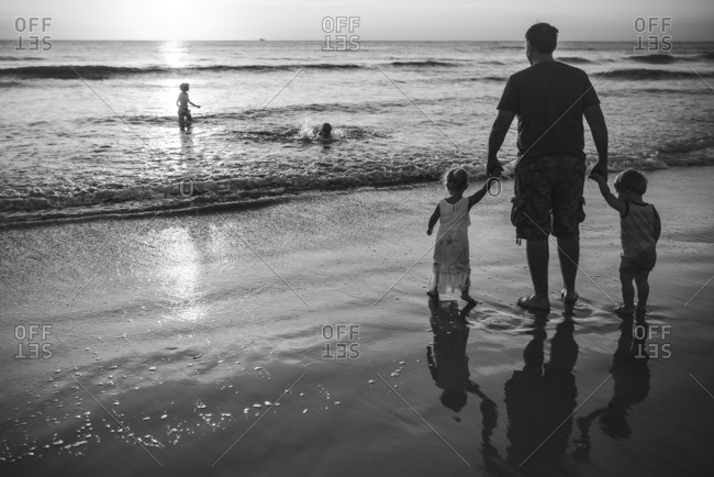 Father walking with toddlers in the ocean in black and white