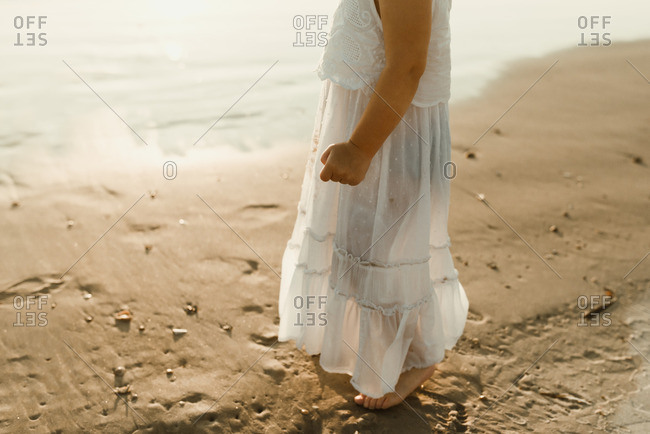 Little girl standing barefoot in a white dress on a beach