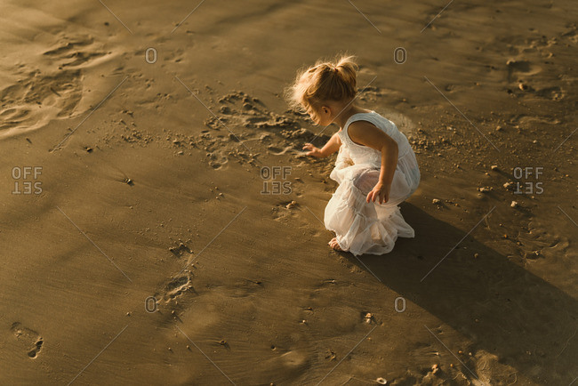 Little girl playing in a white dress on a beach