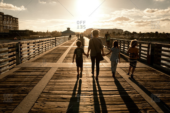 Mother walking with children on a boardwalk at sunset