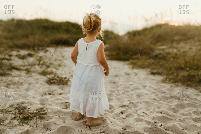 Little blonde girl walking in the sand in a white dress
