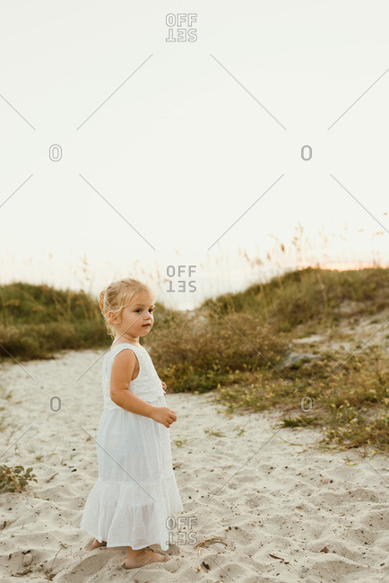 Little blonde girl walking on a sandy beach in a white dress