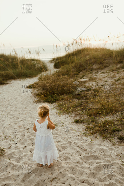 Little blonde girl standing in the sand in a white dress
