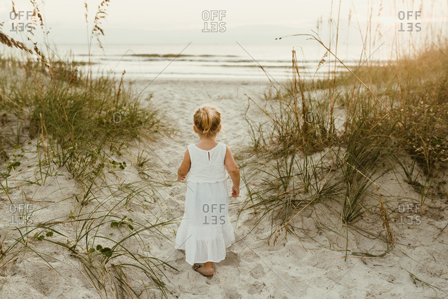 Little blonde girl walking towards the ocean in a white dress