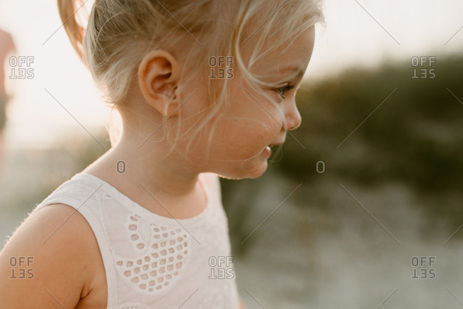 Profile view of a little blonde girl looking away