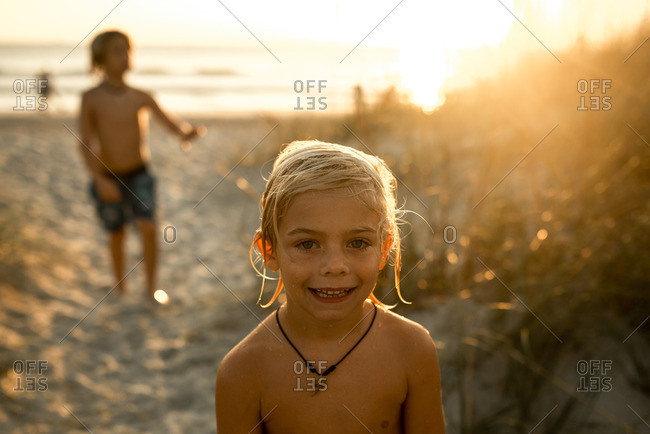 Boys playing on a beach at sunset
