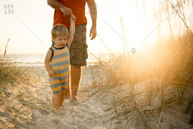 Father walking with toddler son on the beach at sunset