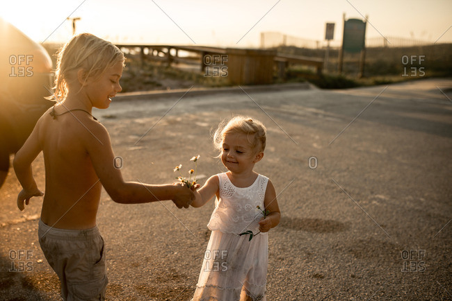 Boy giving little sister flowers by a boardwalk at sunset