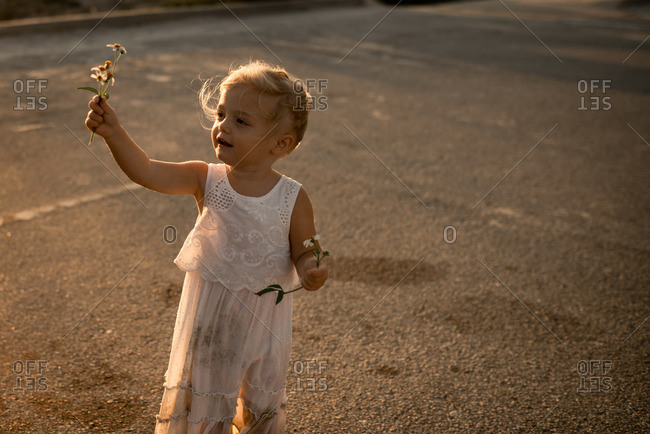 Little girl holding flowers at sunset