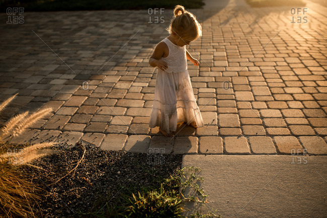 Little girl in a white dress walking on a patio at sunset
