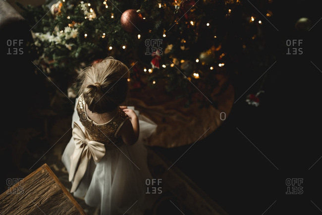 Little girl in a dress looking at a Christmas tree