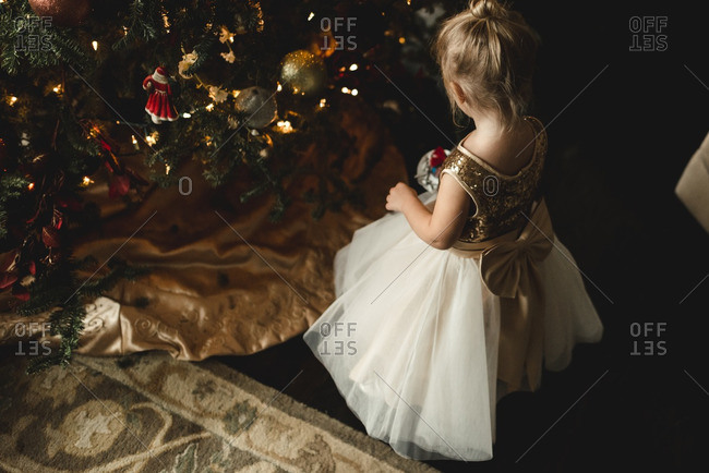 Little girl in a dress kneeling by a Christmas tree