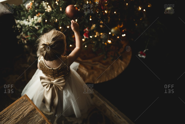 Little girl in a dress touching ornaments on a Christmas tree
