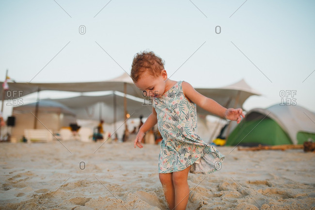 A girl standing in a hole in the sand