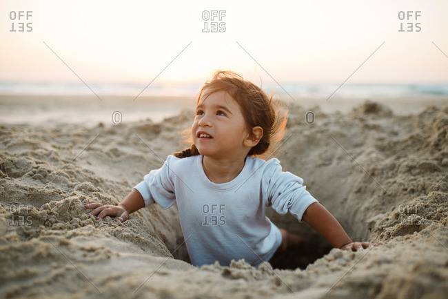 A girl sitting in a hole in the sand