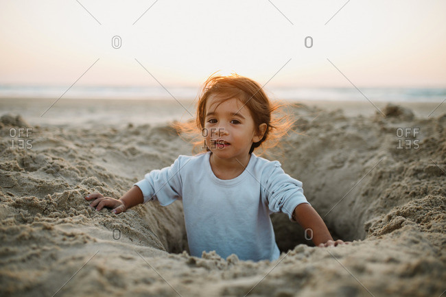 A girl sitting in a hole on a sandy beach