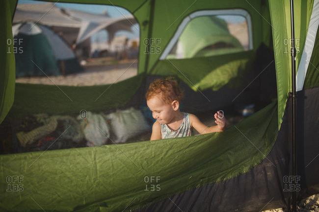 A girl playing inside a beach tent