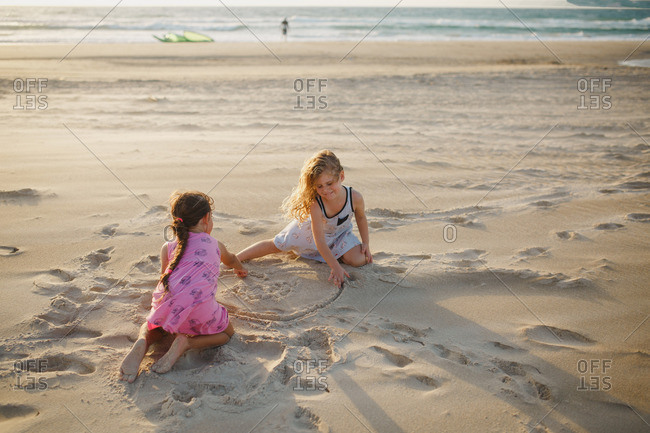 Girls drawing a heart in the sand