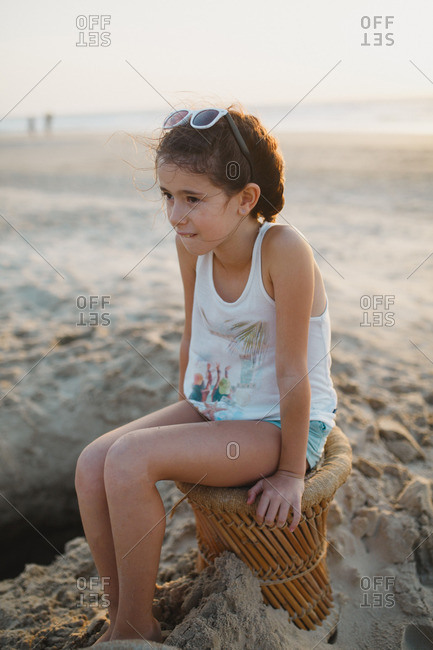 A girl sitting on a beach chair in the sand
