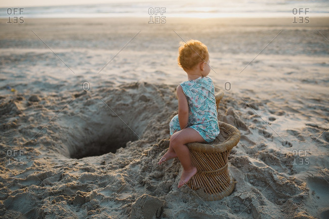 Toddler girl sitting in chair looking back at the sea