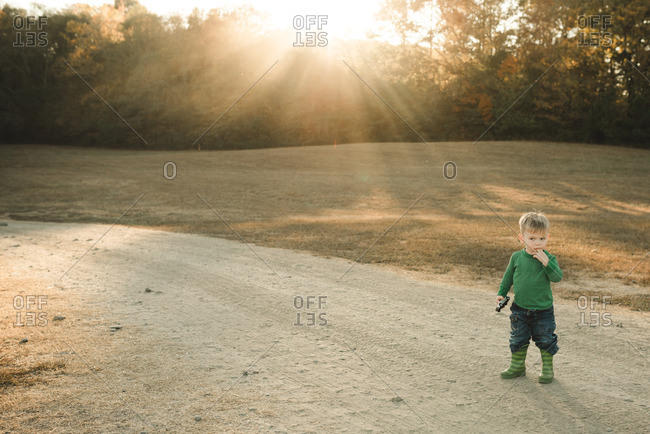Toddler boy standing on a dirt path at sunset