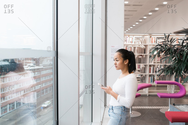 College student texting on her cell phone while looking out a window in a library