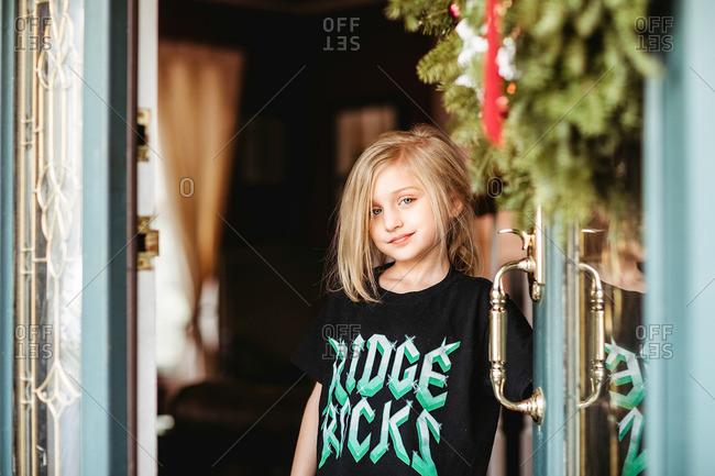 Blonde little girl holding a door open