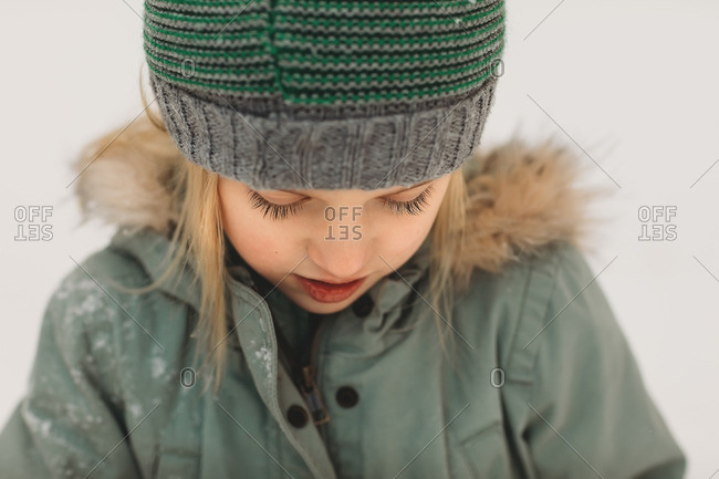 Portrait of a little girl wearing green standing in the snow