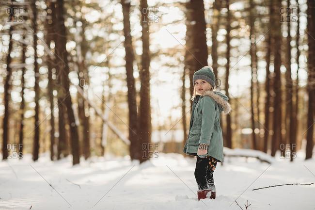 Little girl walking in a snowy forest