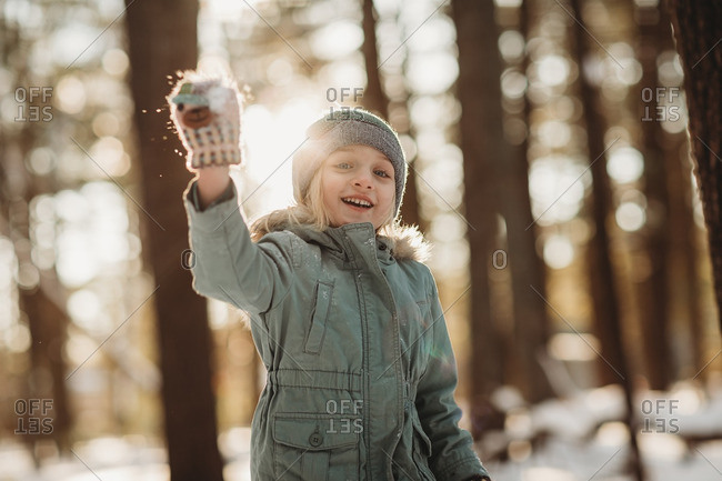 Little girl throwing a snowball in a forest