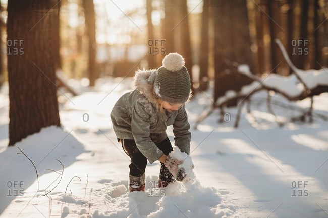Little girl making a snowball in a forest