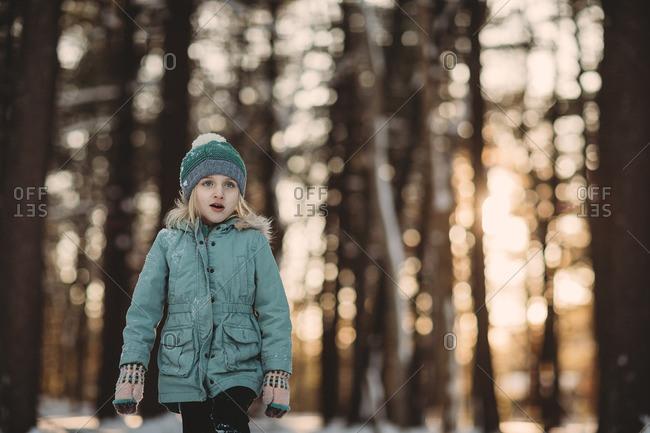 Little girl walking in a wintery forest