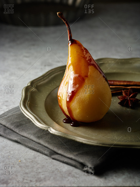 Pear topped with chocolate sauce on a plate with a star anise and cinnamon stick