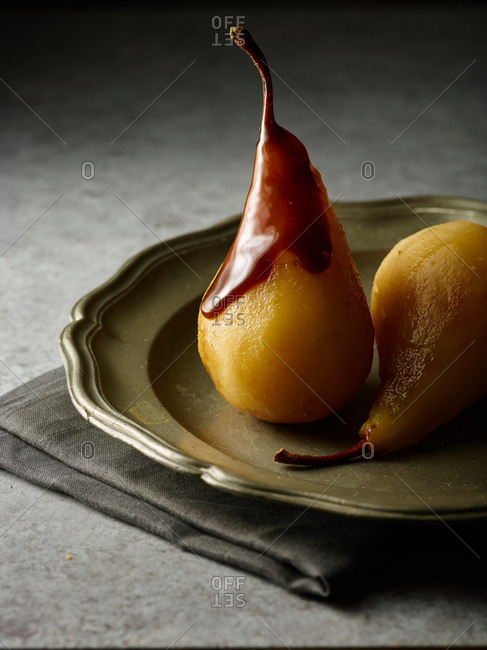 Pears on a plate topped with chocolate sauce