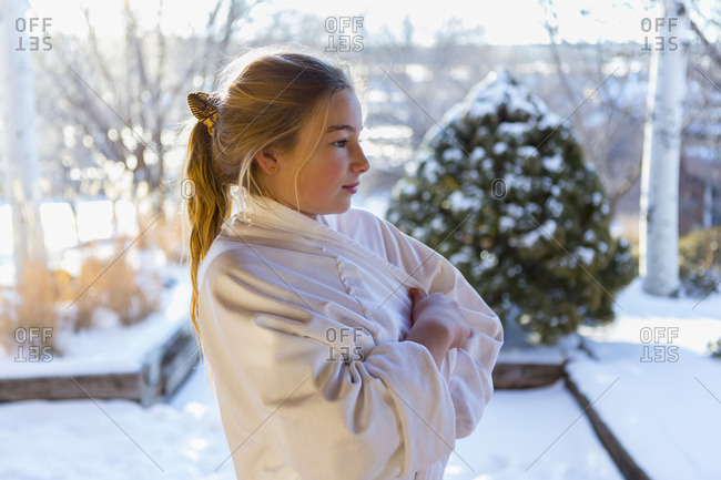 Girl wrapped in a bathrobe outdoors on a winter day