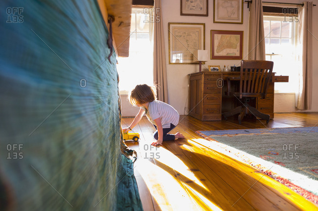 Boy driving toy truck into his play fort