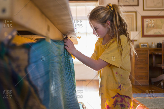 Girl tying blankets on a play fort