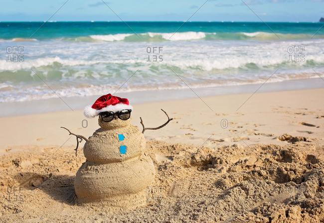 Christmas snowman figure built out of sand on a beach