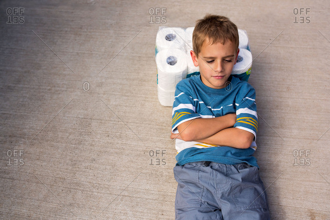 Boy lying down on a package of toilet paper