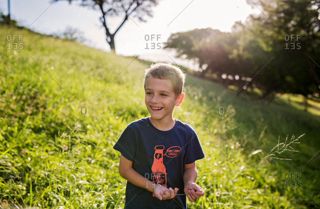 Happy boy standing on a grassy hill