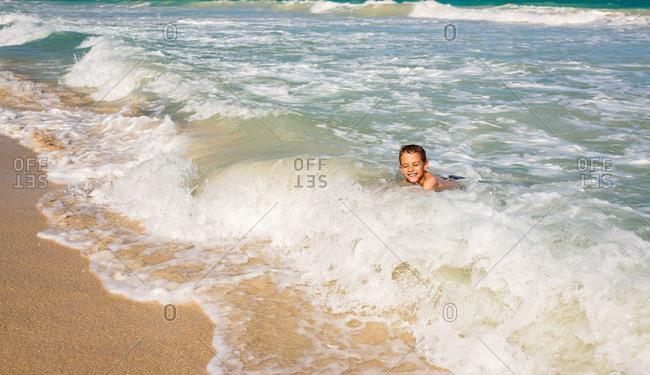 Little boy swimming in the ocean waves