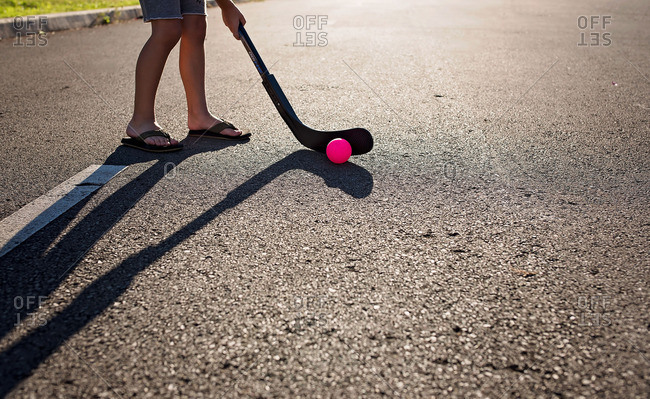 Boy playing hockey in the street with pink ball