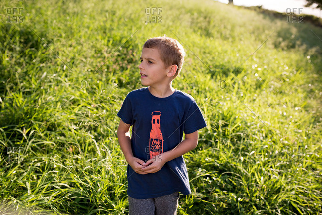 Boy on a grassy hill looking away