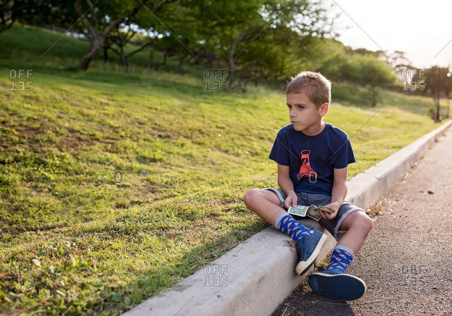 Boy sitting on curb counting money