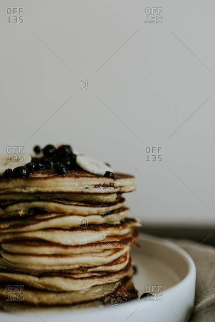 Stack of blueberry pancakes topped with berries and bananas