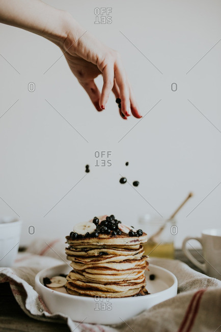 Hand sprinkling berries onto a stack of blueberry pancakes